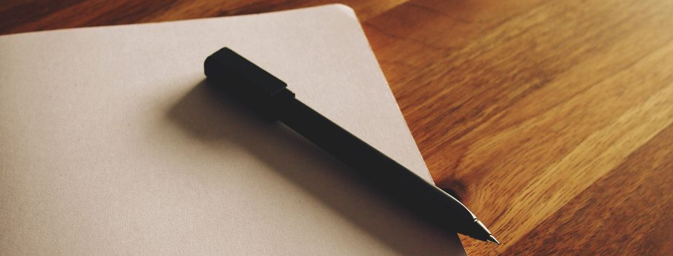black pen and notebook on wooden table